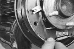 9 Вставьте щупы толщиной 2.0 мм между концевыми ограничителями разжимных рычагов и задних тормозных колодок обоих...