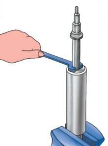 Установка амортизатора в тиски для разборки специальным ключом